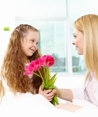 Adorable girl giving bunch of tulips to her mother photo