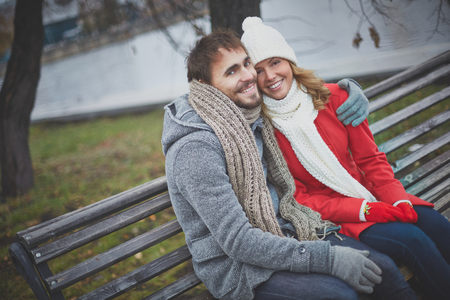 Image of affectionate couple sitting on the bench and looking at camera in park photo