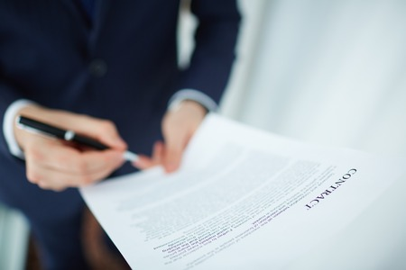 Image of contract being read and signed by businessman photo