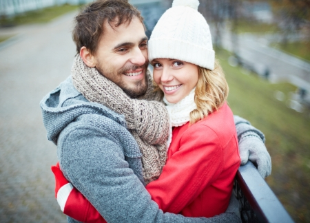 hugging couple: Image of affectionate couple looking at camera in park