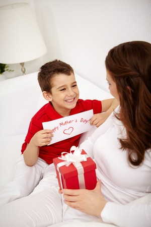gifts: Leuke jongen met feliciteren kaart op zoek naar zijn moeder met giftbox