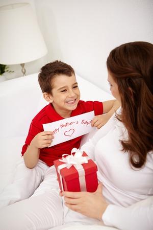 mamma e figlio: Ragazzo carino con congratulandomi con carta guardando sua madre con giftbox