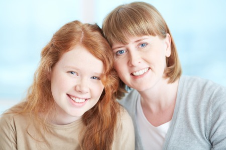 committed: Lovely girl and her mother looking at camera with toothy smiles