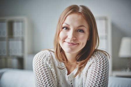 Smiling young woman looking at camera in isolation Stock Photo