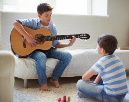 teen boys: Ritratto di un bel ragazzo suonare la chitarra con il fratello vicino