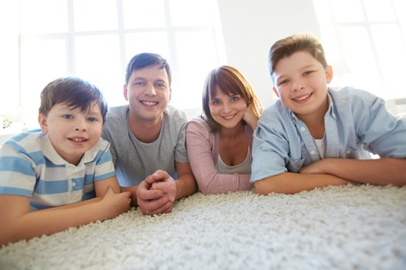 Portrait of happy family of four looking at camera with smiles photo