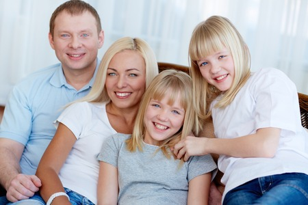 twin sister: Portrait of happy family with twin daughters smiling at camera  Stock Photo