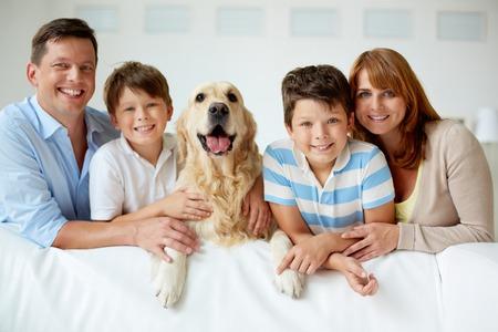 Retrato de familia feliz con su mascota mirando a la cámara