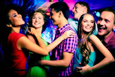 personas festejando: Feliz jóvenes amigos bailando en la discoteca