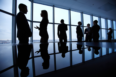 standing against: Group of colleagues standing against window in office and speaking