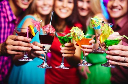 Glazen met cocktails in handen van gelukkige vrienden op feestje Stockfoto