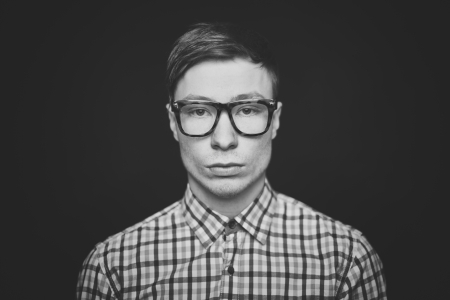 Face of young guy in eyeglasses looking at camera