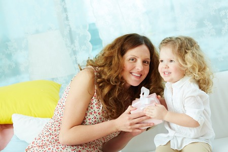 Kind mother giving her daughter small present in giftbox photo