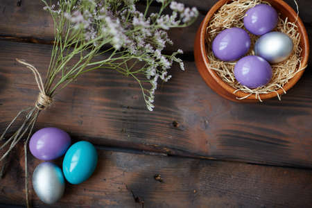 creative egg painting: Colorful Easter eggs and dry flowers near by Stock Photo