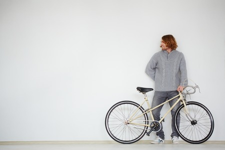 weekend activities: Portrait of a handsome man with bicycle in isolation Stock Photo