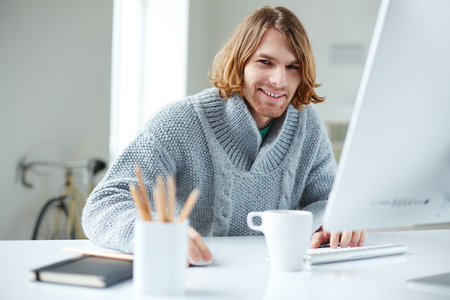 one young man: Portrait of handsome man working with computer in office