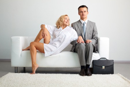 Photo of serious man in suit sitting on sofa with seductive happy woman near by Stock Photo