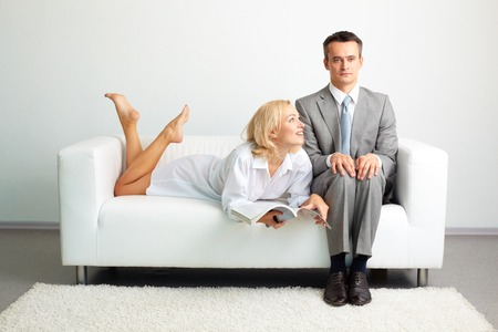 Photo of serious man sitting on sofa with happy woman with magazine lying near by photo