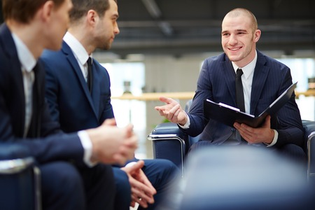 Group of young businessmen communicating at meeting Stock Photo