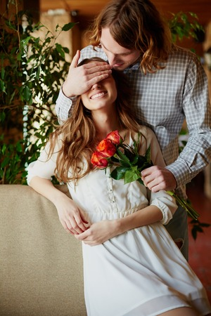 eyes closing: A young man giving bunch of red roses to his girlfriend while closing her eyes Stock Photo