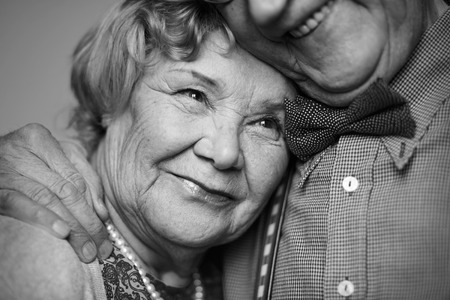 Black-and-white image of senior female being embraced by her husband Stock Photo