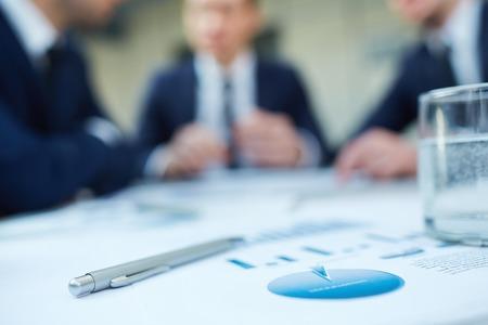 Afbeelding van zakelijke documenten en pen op de werkplek met een groep collega's interactie op de achtergrond