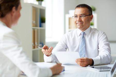 Portrait d'homme d'affaires d'âge mûr en regardant son secrétaire tout en parlant à son