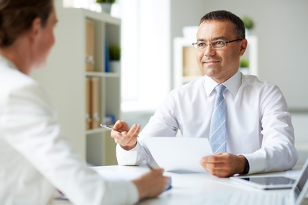Portret van volwassen zakenman op zoek naar zijn secretaresse tijdens het spreken aan haar