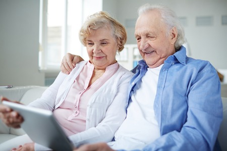 Senior couple with touchpad sitting at home and networking photo