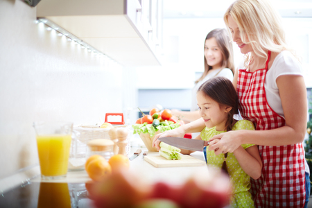 Portrait of happy mother and two daughters cooking in the kitchen photo
