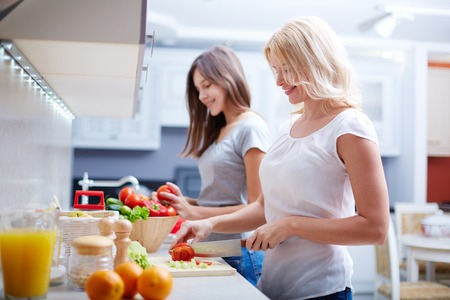 Portrait of happy mother and her daughter cooking in the kitchen photo