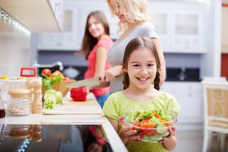 niños cocinando: Retrato de niña feliz con ensalada de verduras en el fondo de su madre y hermana cocinar Foto de archivo