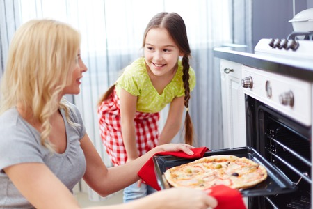 pizza oven: Portrait of young woman taking pizza out of oven with her daughter standing near by Stock Photo