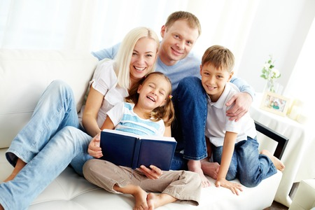 Portrait of happy family with two children looking at camera and laughing  Stock Photo
