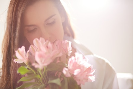 Portrait of lovely lady looking at flowers and smelling them Stock Photo