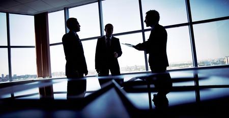 Shady beeld van een manager bespreken zakelijke aangelegenheden met zijn ondergeschikten