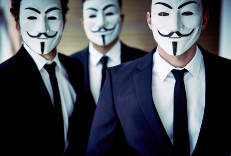 featureless: Portrait of unrecognizable people wearing Guy Fawkes masks and business suits