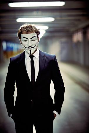 匿名のマスクの後ろからじっとビジネス男の垂直方向の肖像画 報道画像