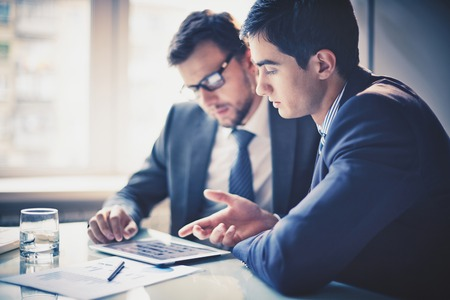 reunion de personas: Imagen de dos j�venes empresarios que usan el touchpad en la reuni�n Foto de archivo
