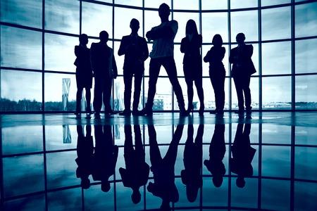 Business team debout contre la fenêtre avec le leader en face