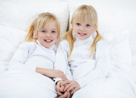 younger: Portrait of cute twins lying in the bed  Stock Photo