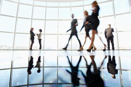 Verschillende witte boorden werknemers communiceren in het kantoor tegen venster met drie collega's een wandeling door de buurt door