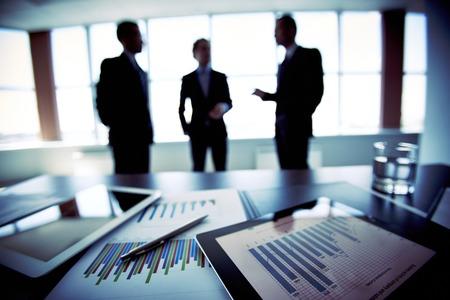 Close-shot van een tablet-computer weergeven van financiële gegevens, drie zakenlieden staan