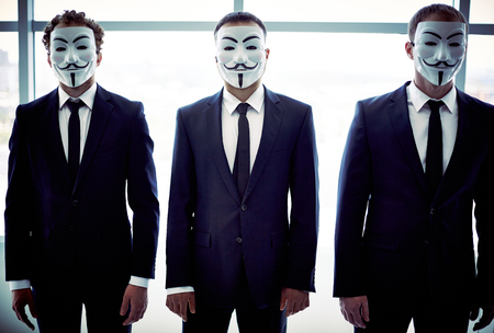 featureless: Portrait of three colleagues hiding behind Guy Fawkes masks