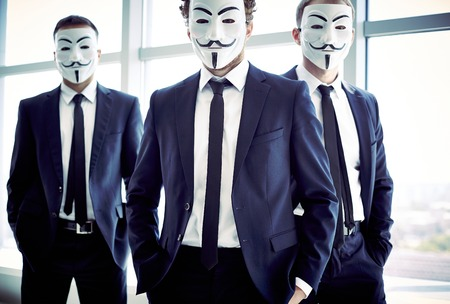 vendetta: Portrait of three masked guys in business suits Editorial