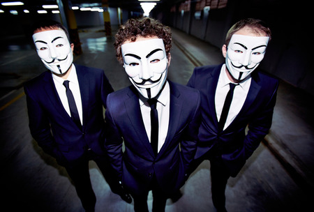 Portrait of three guys in Guy Fawkes masks with intense looks and formal appearance