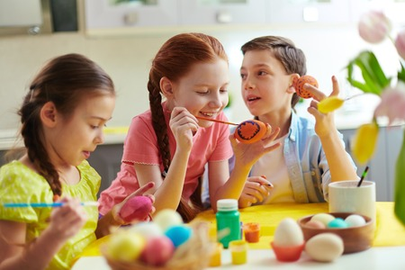 Photo of cute kids painting Easter eggs at home photo