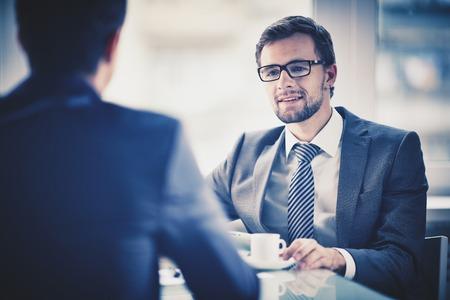 Imagen de joven hombre de negocios con una taza de café se comunica con su colega Foto de archivo