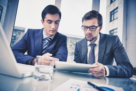 Image of two young businessmen discussing document in touchpad at meeting photo