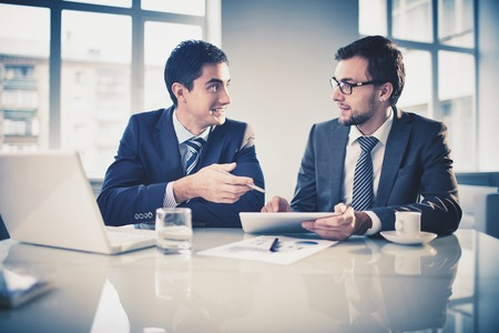 busy office: Image of two young businessmen communicating at meeting
